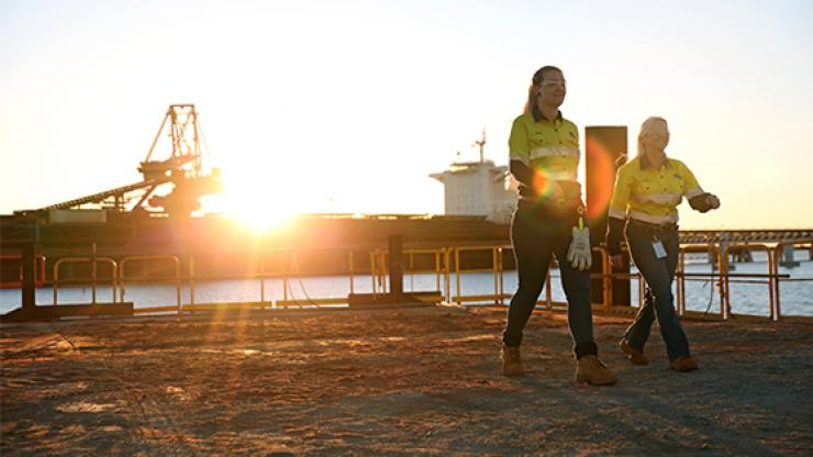 Two female workers in high vis walking through Fortescue Metals site