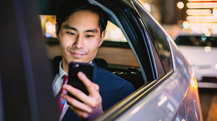 Man in car looking at phone