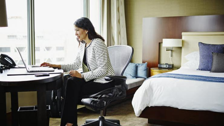 Woman sitting at desk in hotel room using laptop
