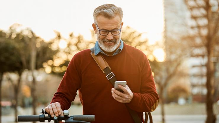 Man looking at phone on sidewalk with bicycle.