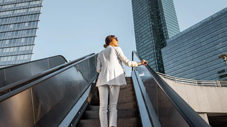 Stylish businesswoman in white suit going up on the escalator at the business centre outdoors with skyscrapers on the background
