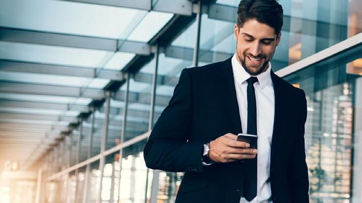 Businessman looking at phone happily