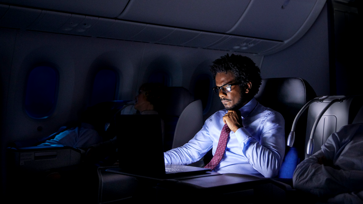 Business man working while on a flight