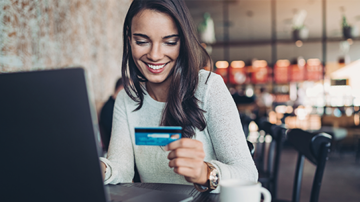 Woman looking at credit card while booking travel online.