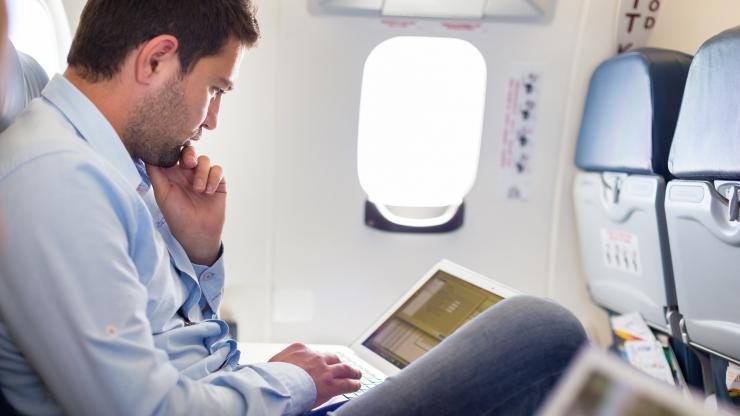 Man reading latest travel industry update on laptop
