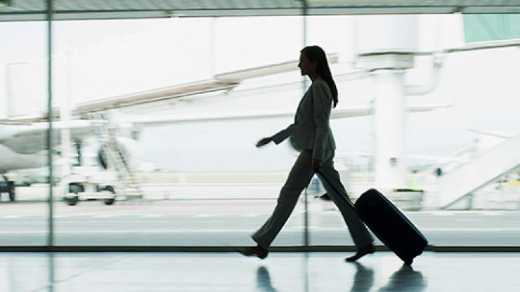 Business woman walking in airport against the aeroplane background