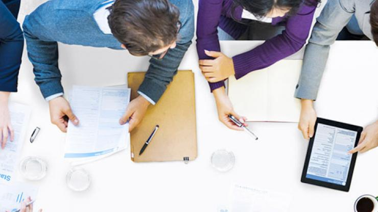 Employees working in group at office desk with reports and statistics