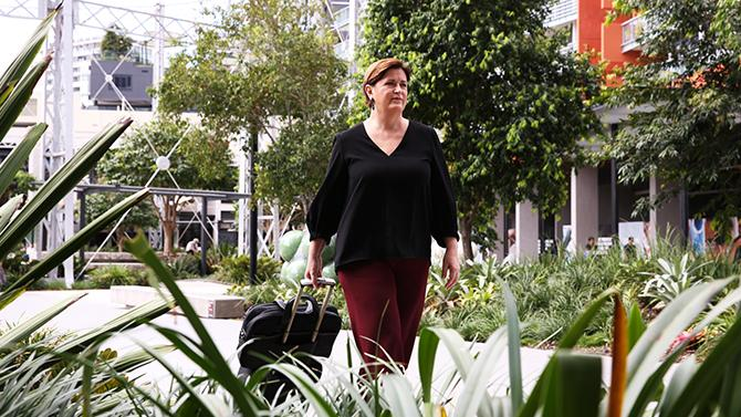 Bank of Queensland employee walking with suitcase