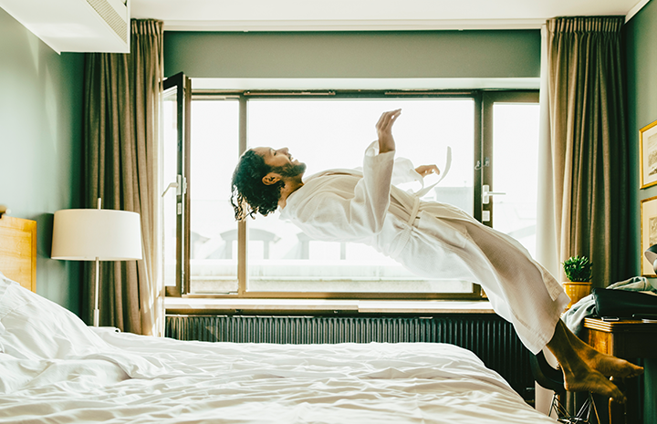 Man in robe jumping onto bed